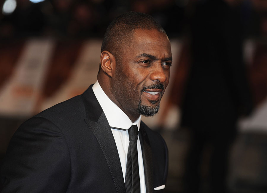 Edris Elba in black suit white shirt and black tie