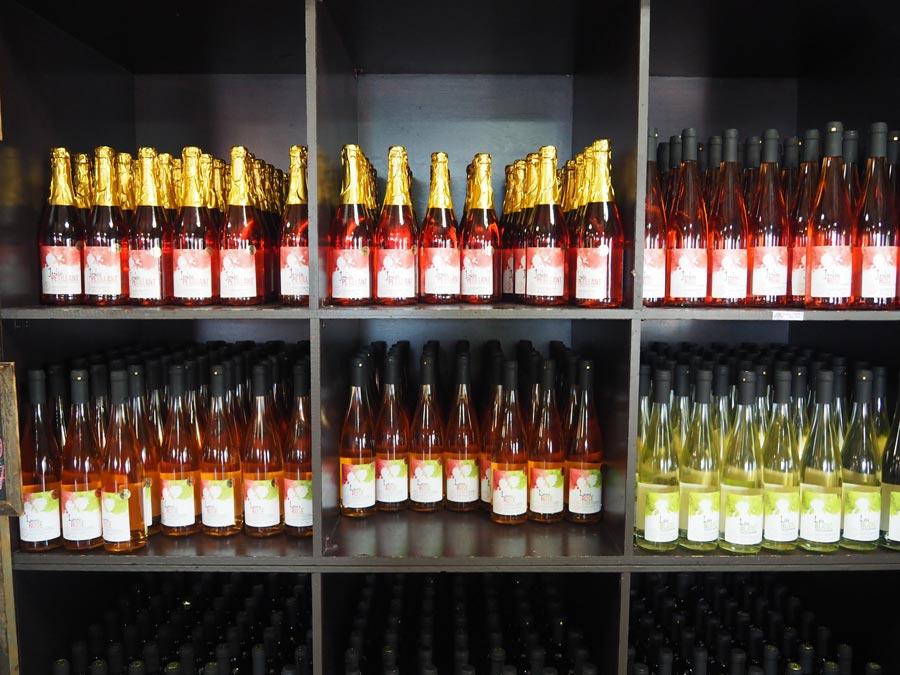 A shelf full of strawberry wine.