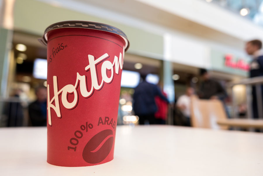Red Tim Hortons coffee cup on a table with customers lining up in the background.