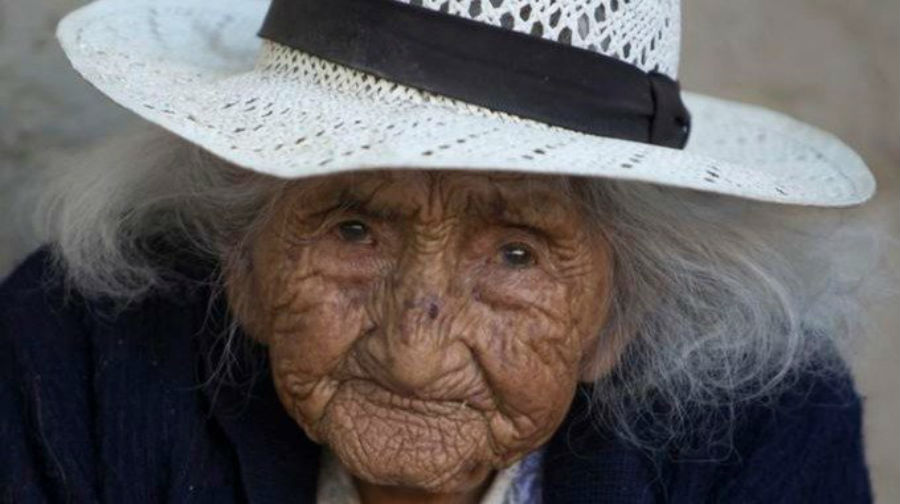 Photo of Bolivian woman believed to be oldest person living wearing a white sunhat and smiling.