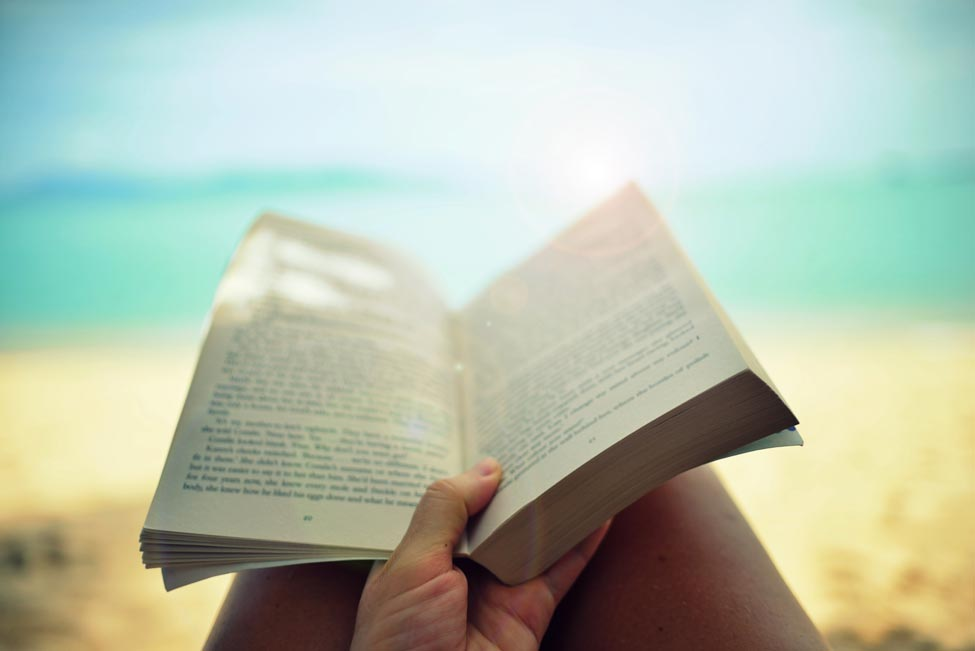 A woman reading a book on the beach.