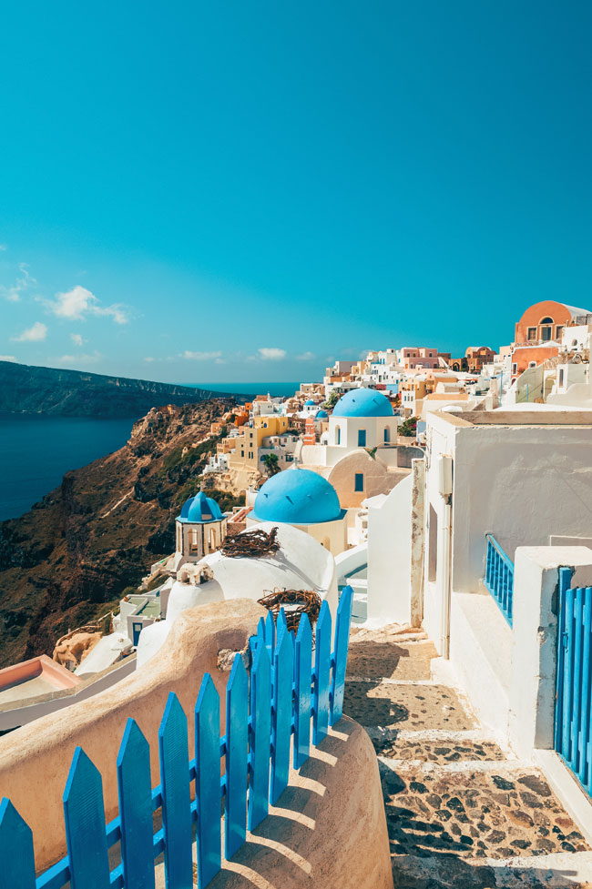 A view of a cliffside town in Santorini featuring multiple spherical roofs and multicoloured structures.