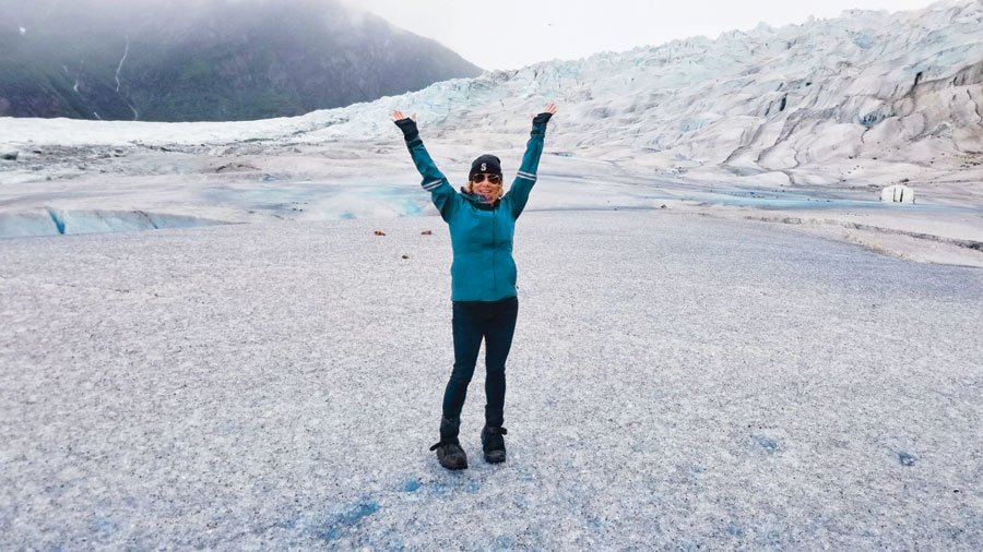 Vivian Vassos with her armed stretched over her head as she stands on the solid ice of Mendenhall Glacier.