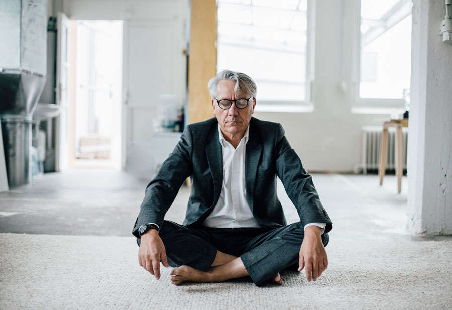 A man wearing thick black framed glasses sitting with his legs crossed and eyes closed in meditation.