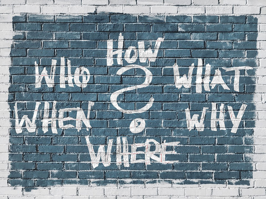 A question mark surrounded by the words how, who, what, when, why and where written on a brick wall.