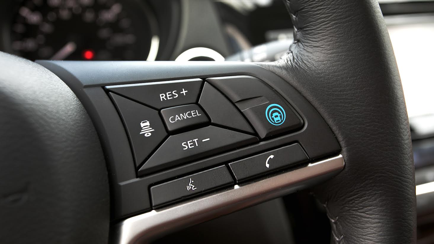 Close up of a steering wheel that features a new auto pilot feature.