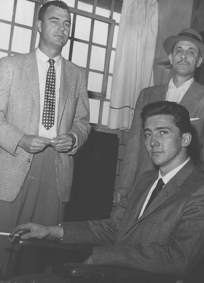End of a 17-Day Spending Spree Cigarette in his hand, Boyne Lester Johnston sits in the office of the Denver jail building after telling of his Canadian bank theft and the spending spree that followed. Standing behind chair are Denver Detectives Clyde Villano (left) and Joe Talty.