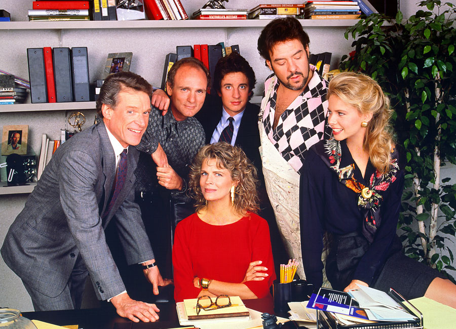 The cast of Murphy Brown gathered around an office desk.