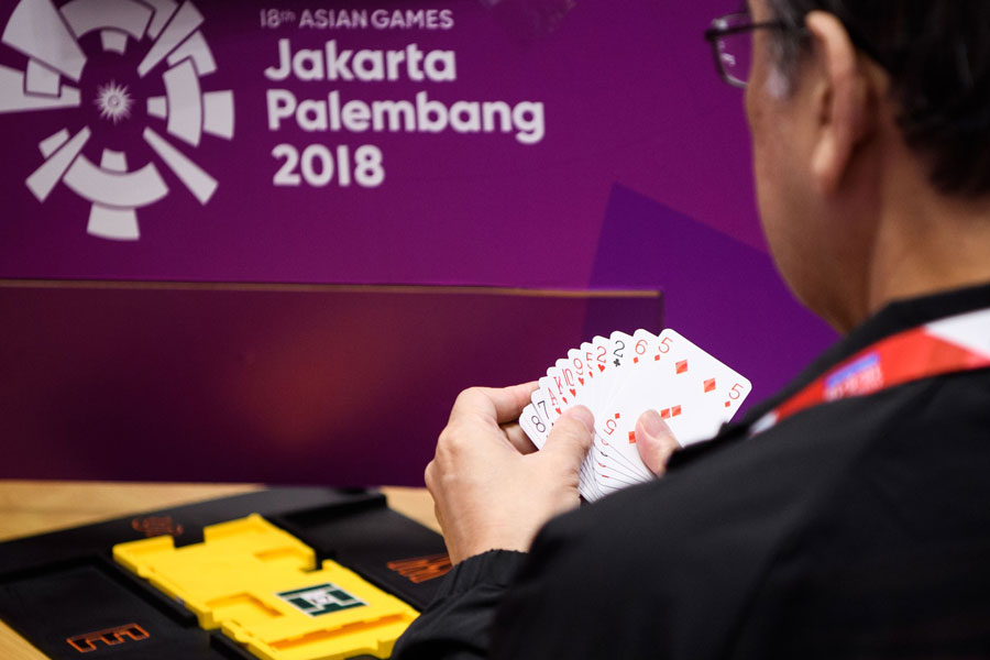 A photo of a competitor playing bridge at the asian games.