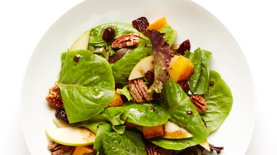 A colourful Squash, pecan and pear salad in a white bowl.
