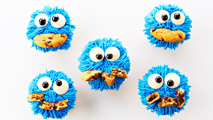 Blue cookie monster cupcakes with googly eyes and a cookie chunk for a mouth.