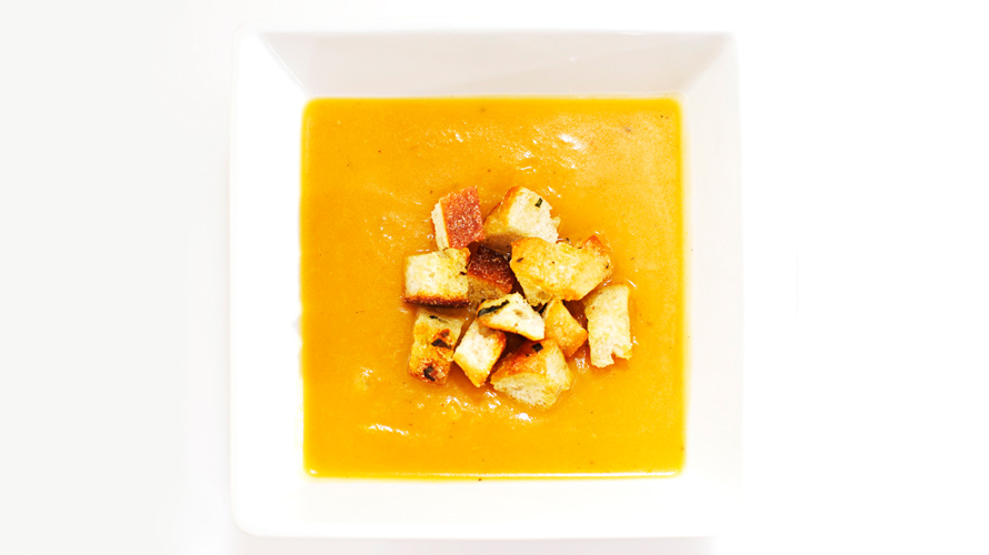 Squash soup in a white square bowl.