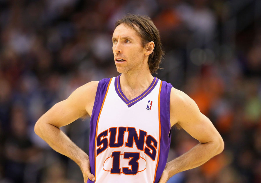 Steve Nash wearing his purple and white Suns jersey with his hands on his hips.