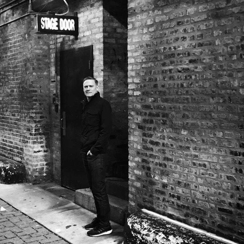 A black and white photo of Bryan Adams at a stage door with his hands in his pockets.