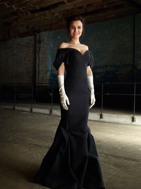 Samantha Barks as Vivian Ward in Pretty Woman the musical wearing a dark blue gown, white gloves and a diamond necklace.
