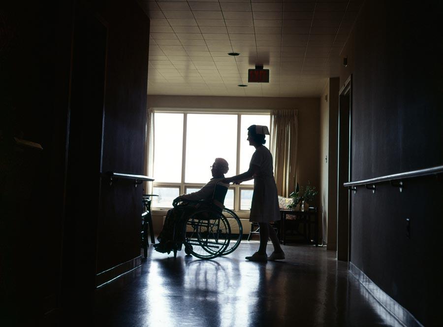 A nurse pushing a woman in a wheelchair in a nursing home.