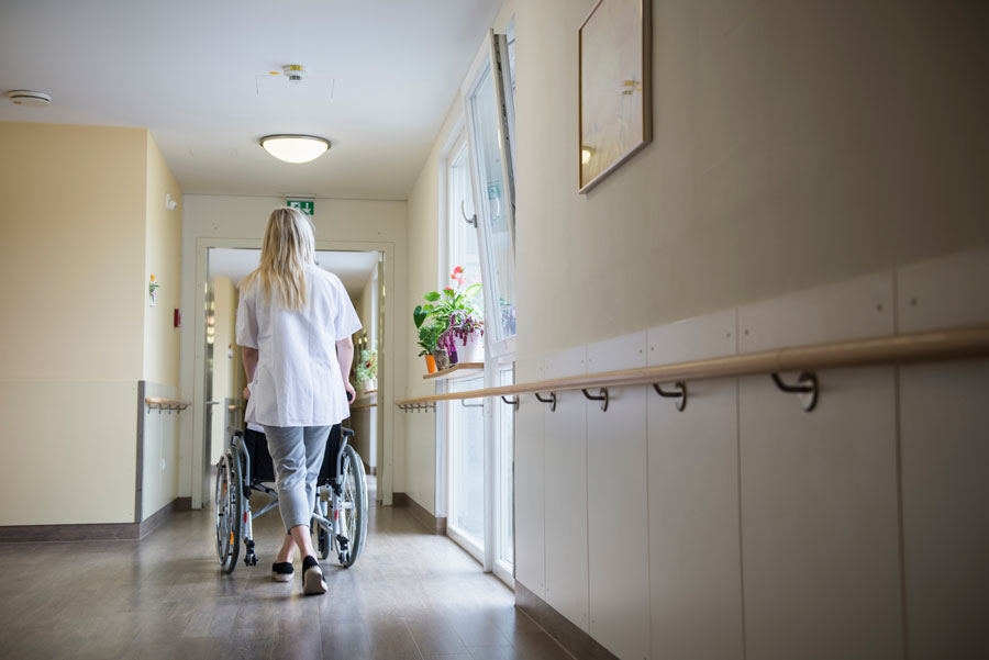 A woman pushing a wheelchair down a hallway.