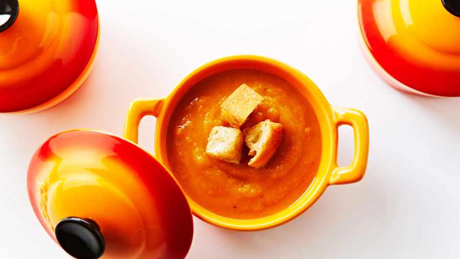 Butter nut squash and sweet potato soup in an orange cup.