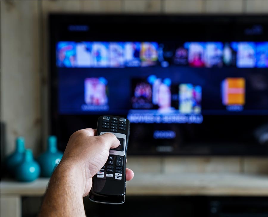 A hand holding a remote pointed toward a TV.
