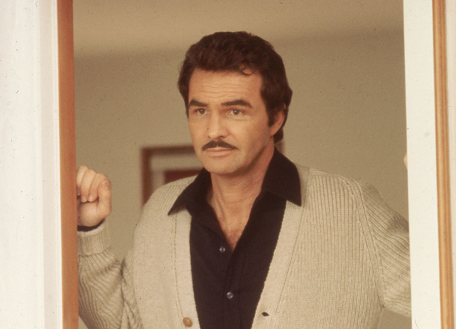 Burt Reynolds standing at a doorway sporting his signature mustache and his collar flared out.