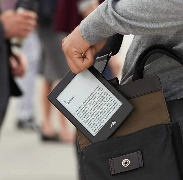 Someone pulling an eReader out of a satchel.