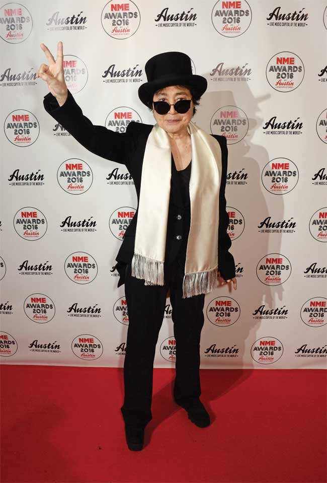 Yoko Ono throws up a piece sign at a red carpet event dressed in a black suit and a gold scarf.
