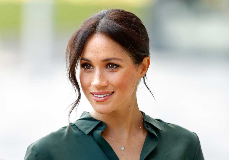 Meghan Duchess of Sussex smiling wearing a green blouse.