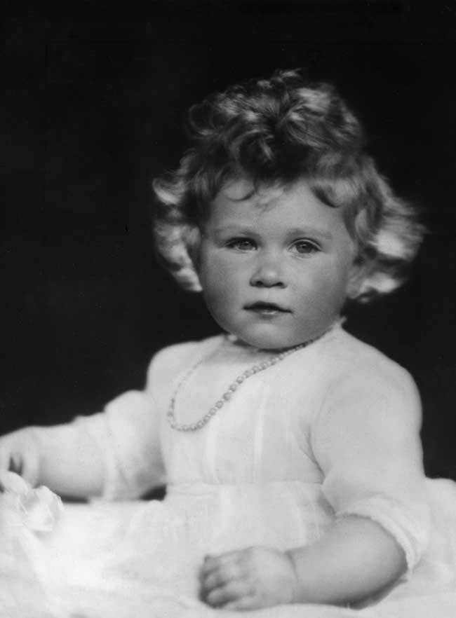 Queen Elizabeth as an infant wearing a white dress.