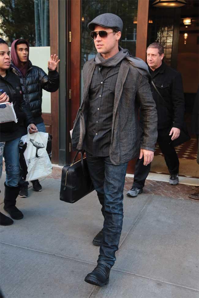 Brad Pitt in a newspaper boys hat wearing dark clothing.