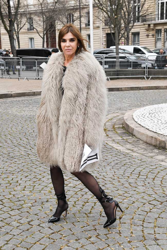 Carine Roitfeld wearing a large beige fur coat with black nylons and high heels.