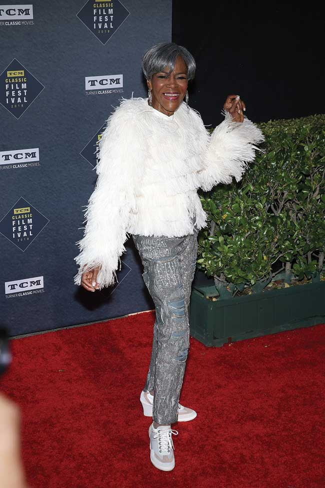 Cicely Tyson strikes a pose with a shimmery white feather coat and dark silver slacks.