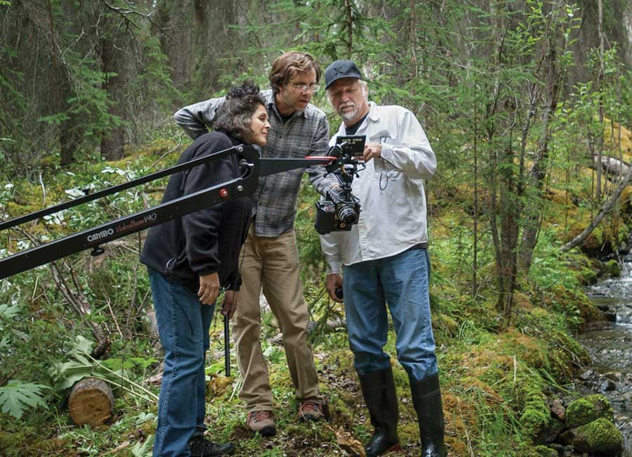 Burtynsky and filmmakers Jennifer Baichwal and Nicholas de Pencier working on Anthropocene multimedia project in a heavily wooded area.