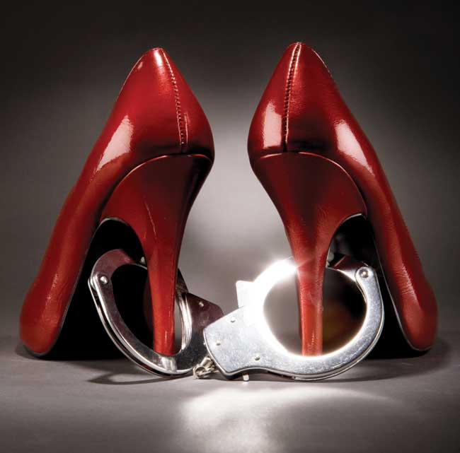 A pair of red high heels with a pair of handcuffs around the heel.
