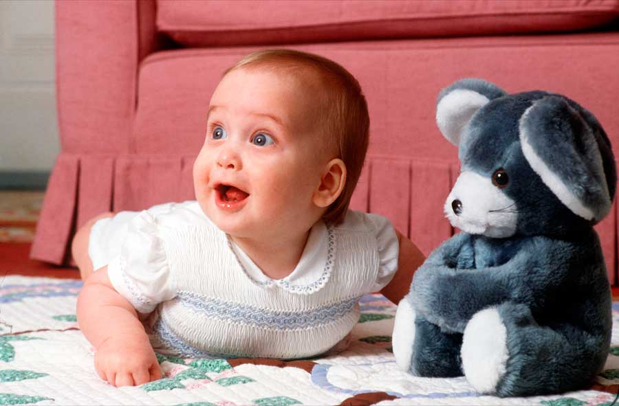 Prince William as an infant posing beside a stuffed bear.