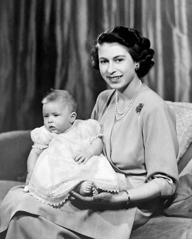 Prince Charles as an infant in a white nightgown sitting on his mother's lap.