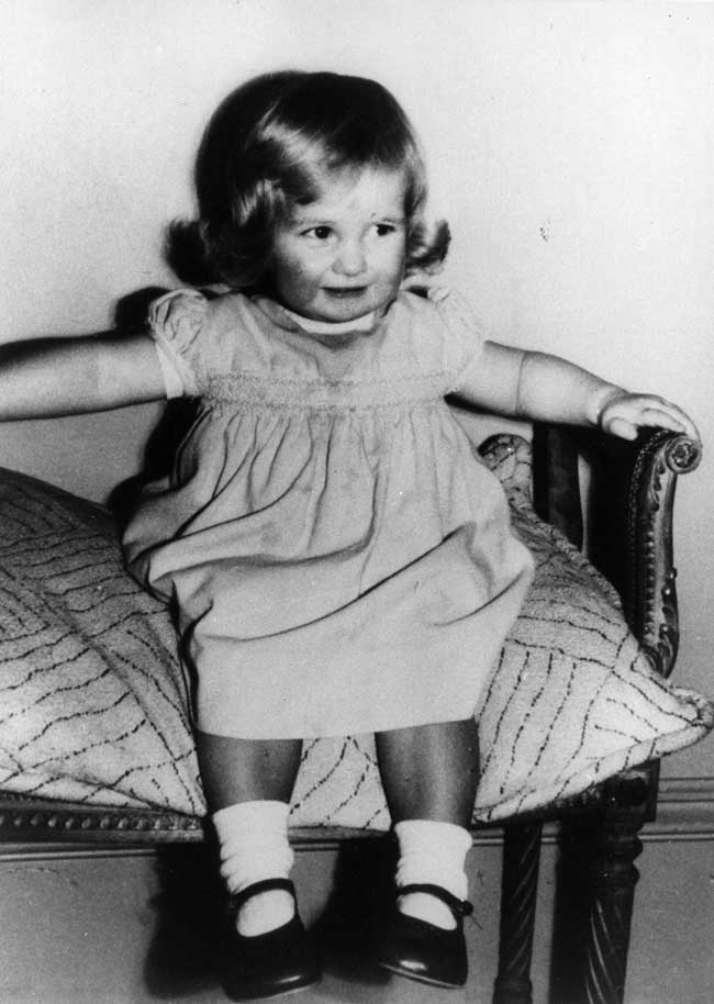 Princess Diana as a toddler sitting on a cushioned chair with her arms resting on the arm rests.