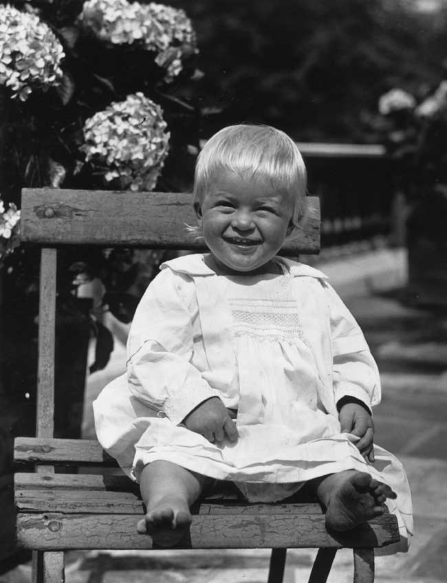 Prince Philip as an infant sitting on a wooden chair squinting and smiling.