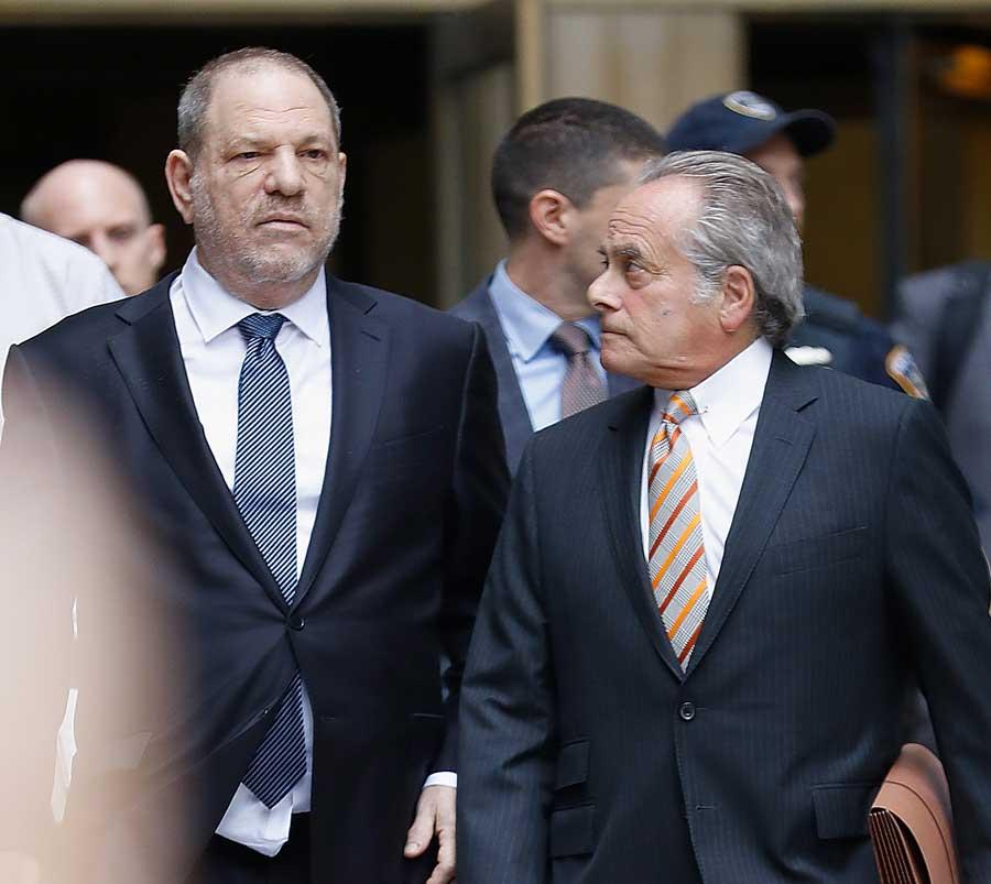 Harvey Weinstein walking alongside his lawyer.