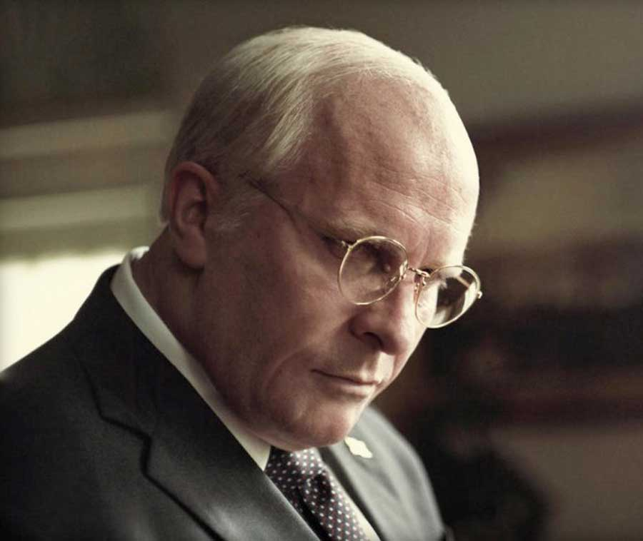 Christian Bale's as Dick Cheney glances down wearing a pari of glasses and a suit.