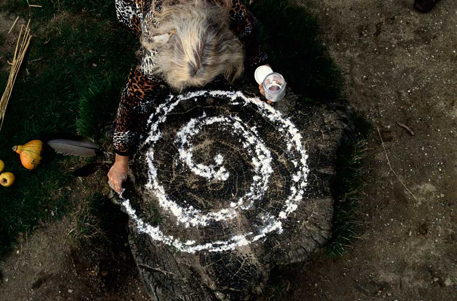 A grey-haired woman pouring salt in a spiral pattern on a dark wooded floor.