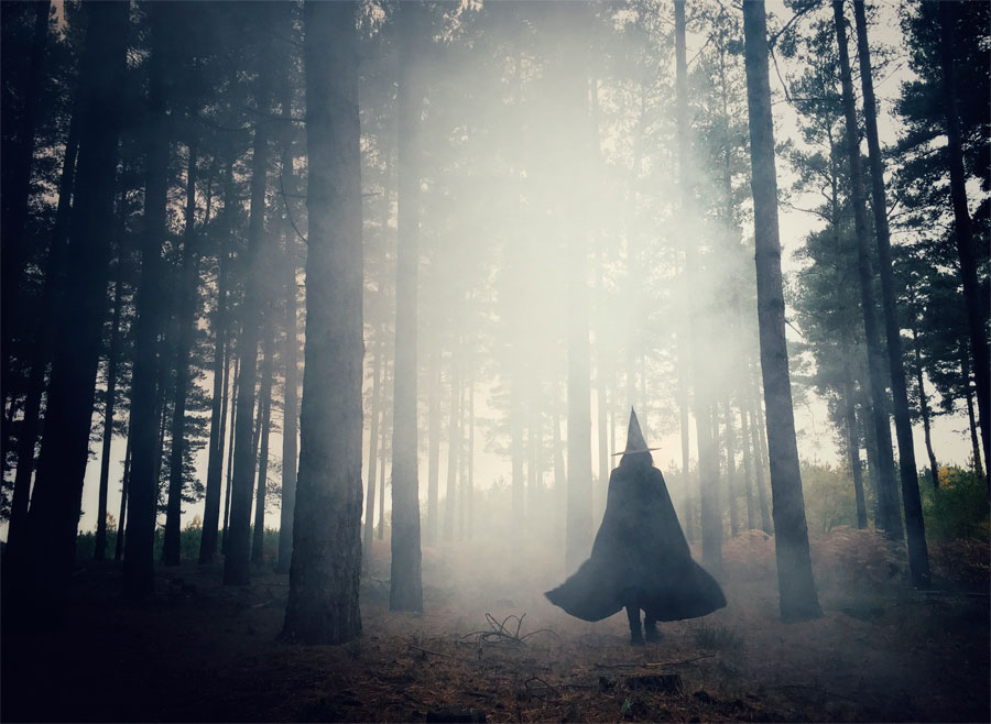 A witch walking through a foggy forrest.