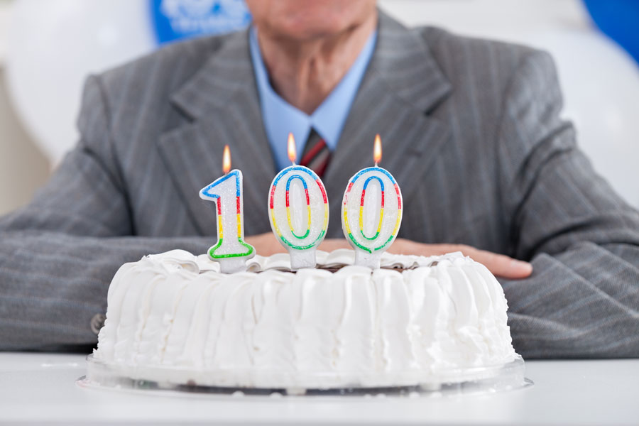 A man sits behind a birthday cake set with a 100 birthday candle
