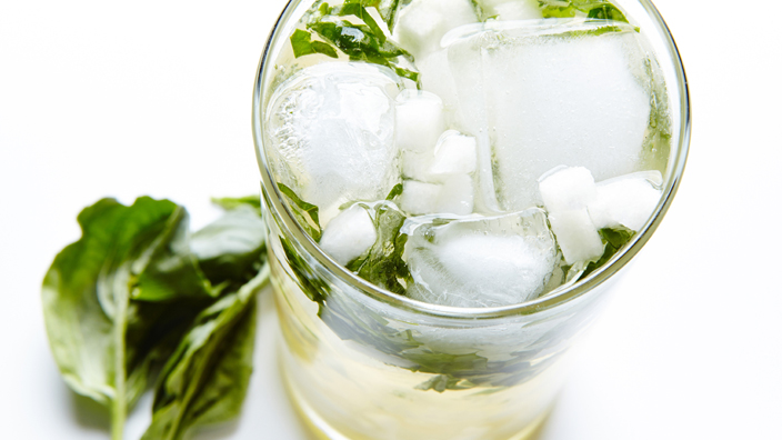 An asian pear mojito in a glass with ice and mint leaves.