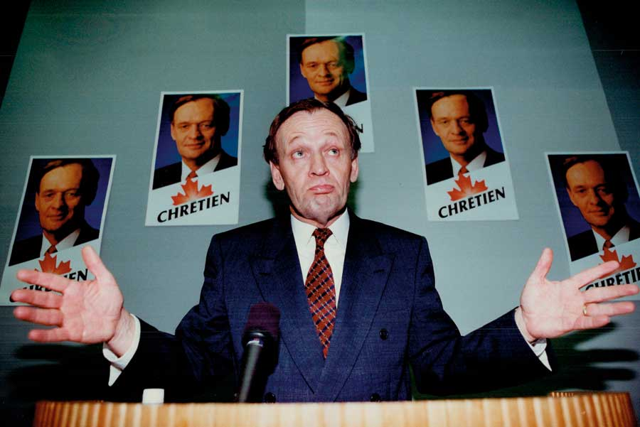 A young Jean Chrétien sitting at a desk with his hands out, palms facing the camera.
