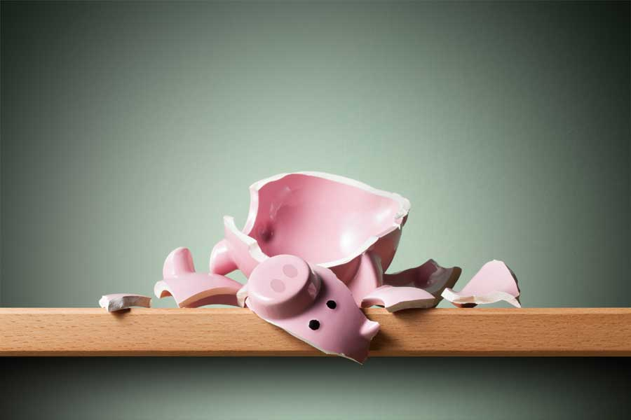 A broken piggy bank with the piece with the face on positioned in the front of the pile.