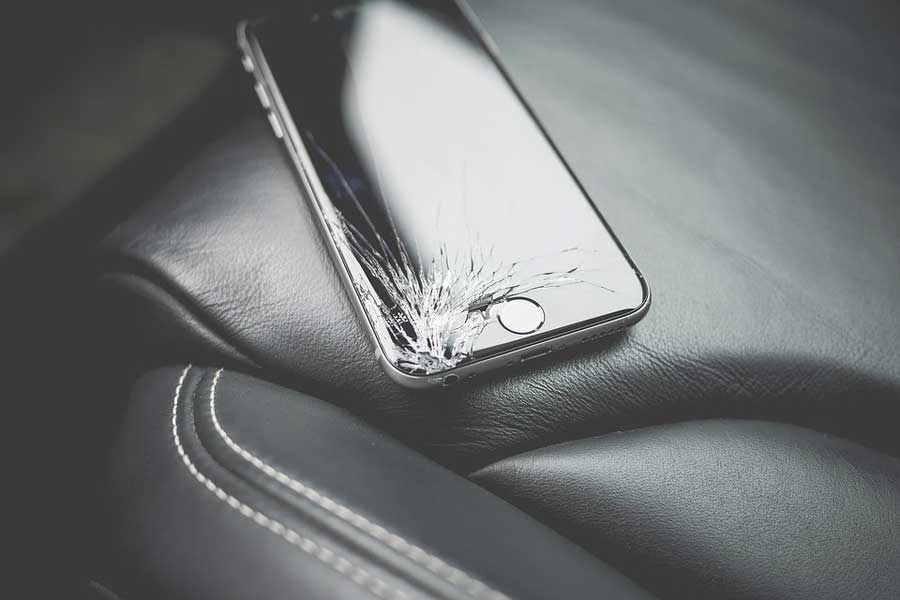A phone on the seat of a car with its screen cracked.