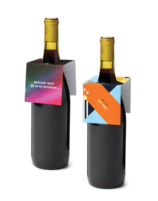 Two bottles of wine shown with gift tags around the bottle neck