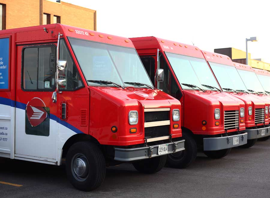 A line of Canada post trucks in a parking lot.