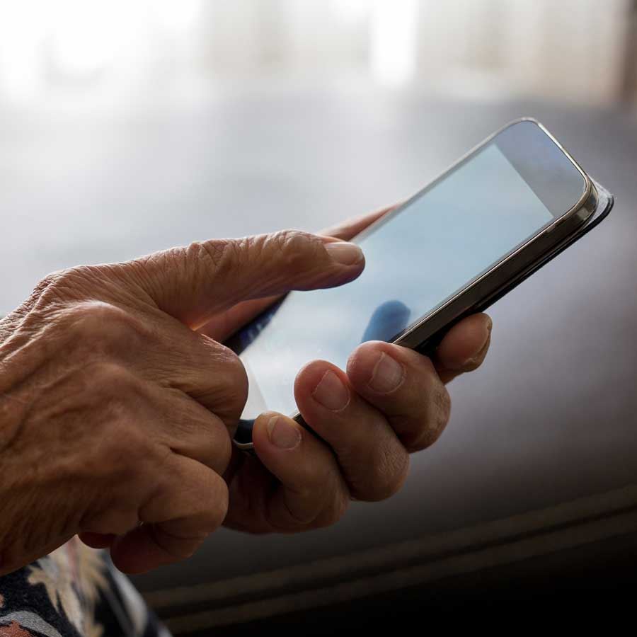An older persons hands operating a cellphone.