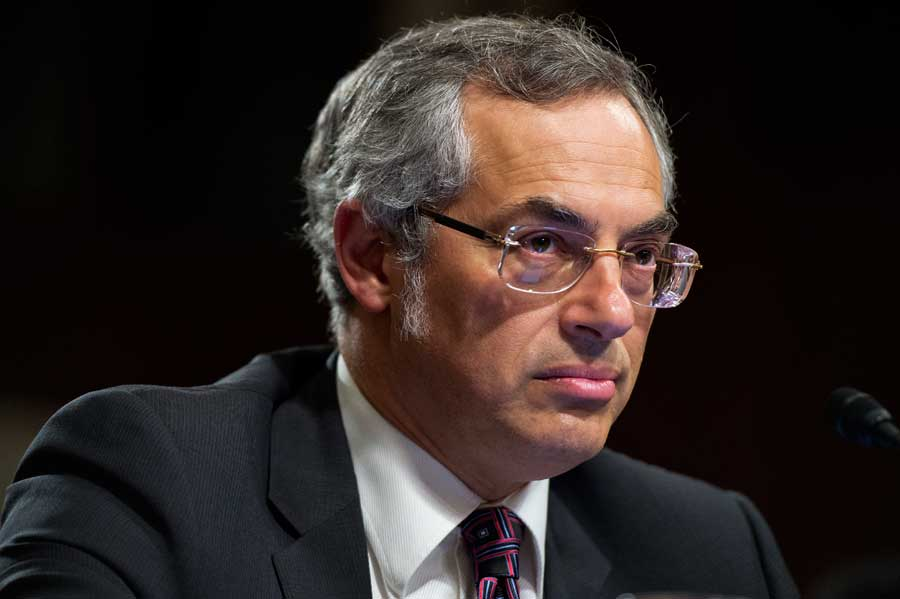 Tony Clement on a black background staring off camera.